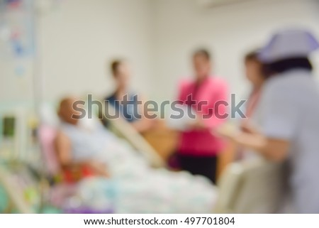 Blur Medical Staff On Rounds Examining Senior Male Patient.