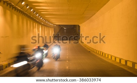 Blur motion group of people riding motorcycles thru a traffic tunnel in Hanoi in early morning. This is the most popular vehicle in Vietnam. Urban traffic concept. Transportation background.