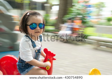 Blur motion images of asian child on merry-go-round - stock photo