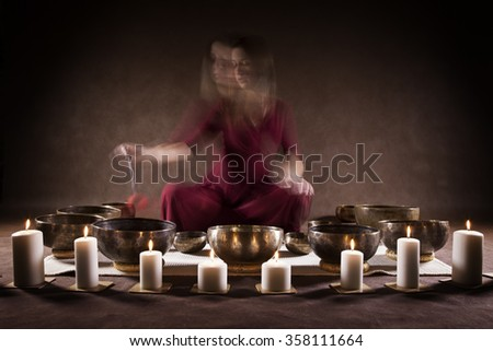 Blur motion of a woman playing a Tibetan bowls, focus on a singing bowls - stock photo