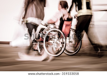 Blur motion of disabled person sit in wheelchair and passengers walking in the airport, vintage filter effect - stock photo