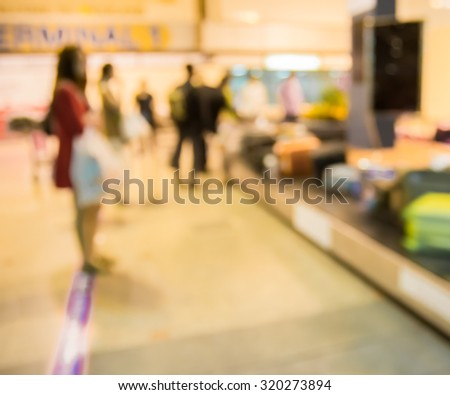 Blur motion of female passenger waiting luggage on conveyor belt in terminal of airport when arrival  - stock photo