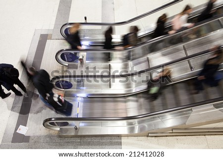 Blur Movement Business people walking on escalator in Rush Hour train station, London, UK