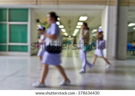 Blur nurses walking in hospital corridor hall - stock photo