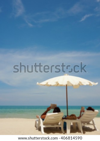Blur of Beach summer couple reading book on island vacation holiday relax in the sun on their deck chairs under a white umbrella. Idyllic travel background with copy space. - stock photo