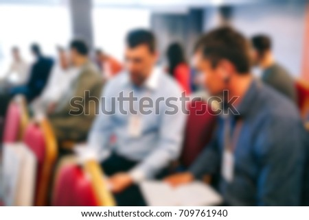 Blur of business meeting in conference hall.