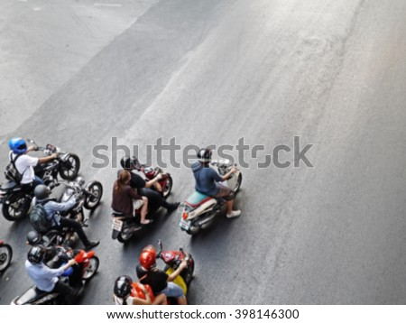 Blur of dense/crowed scene of city traffic in rush hour, crowd of people wear helmet, transport by motorcycle, stop at red light in stress situation. (look like starting point in racing circuit) - stock photo