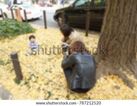 Blur of father taking photo with sitting kid and mother try to get a toddler to look straight at the camera on autumn under Ginkgo tree in the park. Japanese family activities on Sunday concept.