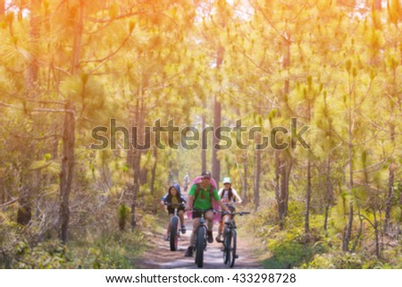 Blur of Happy family on bikes cycling outdoors, active family sport,forest