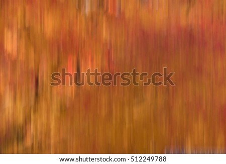 Blur of natural leaf colors in the Fall, specifically, oranges, reds and yellows.  Suitable for background or abstract.