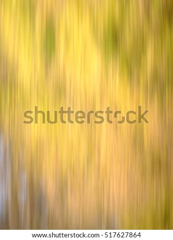 Blur of natural leaf colors in the Fall, with mostly yellow, and a bit of brown, red and green.  Suitable for background or abstract.