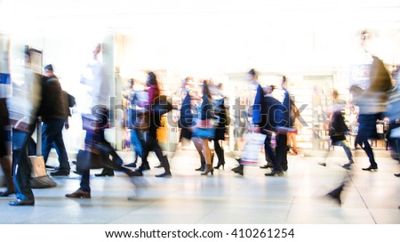 Blur of office workers walking pass the Canary Wharf tube station in early morning rush hours - stock photo