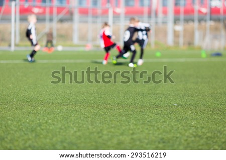 Blur of young kids playing a soccer training match outdoors on an artificial soccer pitch.