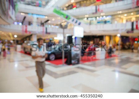 Blur or Defocus Background of People Walking in Shopping Mall with Modern Car show Exhibition booth and Bokeh - stock photo