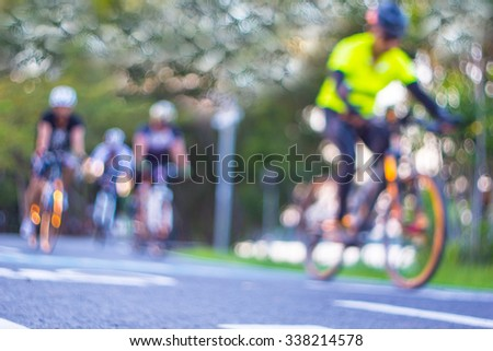 blur photo people and bike are cycling on the road - stock photo