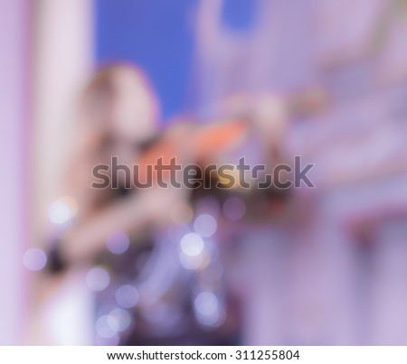 blur pretty young musician playing violin in concert hall - stock photo