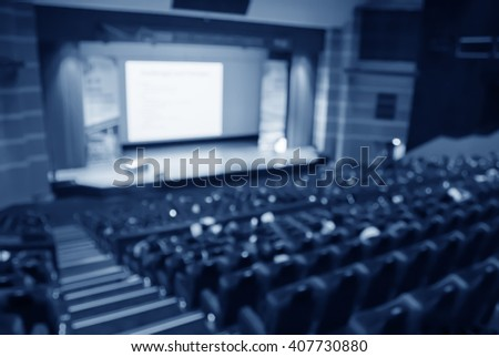 blur  row of blue auditorium or theater or classroom seat and stage with screen - stock photo