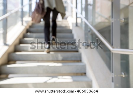 blur stairs background. women's legs go up the stairs - stock photo