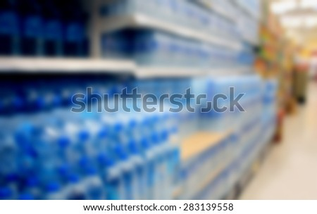 blur supermarket shelves with pack of drink water bottle