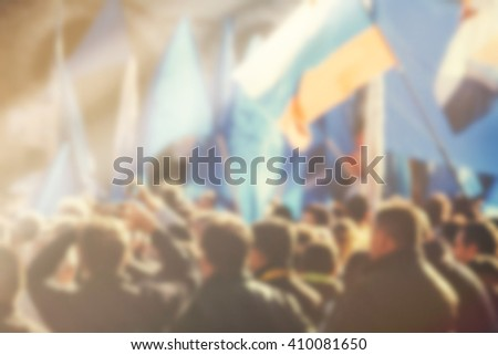 Blur unrecognizable crowd at political meeting, cheering audience looking at the stage and supporting political party, defocussed retro toned image with lens flare. - stock photo