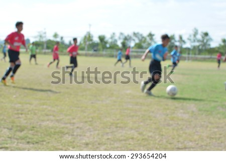 blur young boys playing soccer match on turf. - stock photo
