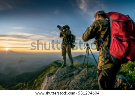 Blur Young man with backpack taking a photo on the top of mountains.