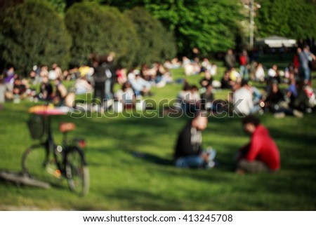 Blured background made of people, who made picnic on the grass in sunny day. - stock photo