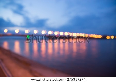 Blured background with bright city lights on a bridge with sky and river. Urban theme - stock photo