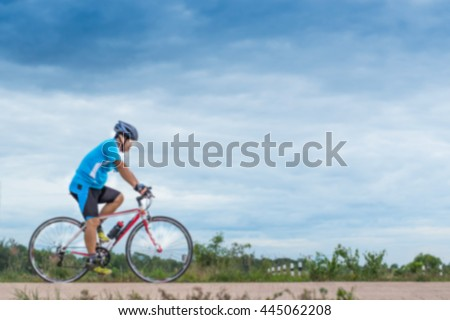 Blurred A man ride the bicycle for exercise,with blue sky and clouds use for background.