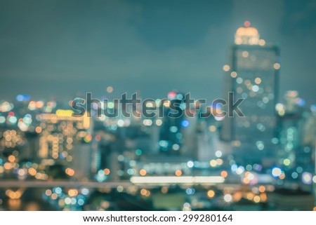 Blurred abstract background aerial view of Bangkok downtown city lights with colorful bokeh night lights in cool vintage color tone:  Blurry city nightlife holiday travel lifestyle bokeh background - stock photo