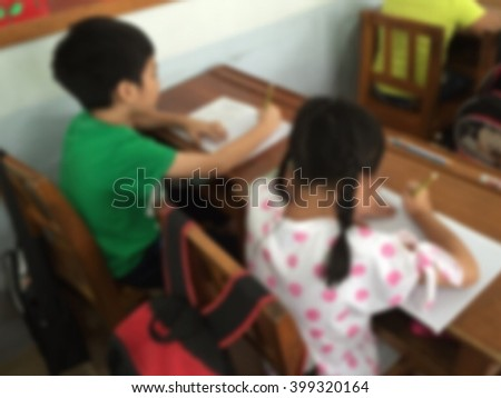 Blurred abstract background Asian Thai students sitting in seat rows in classroom during school/ college examination: Blurry perspective view inside exam room from back of the class in university - stock photo