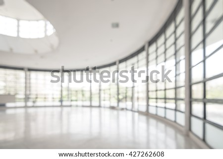 Blurred abstract background exterior view looking out toward to empty office lobby and entrance doors and glass curtain wall with frame: Blurry perspective of reception hall to building entry/ exit - stock photo