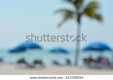 Blurred abstract background image of beach with umbrellas and palm  tree. - stock photo