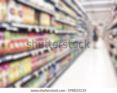 Blurred abstract background inside grocery store/ supermarket: Shelves of dry food product & diary supplies: Blurry perspective view indoor space of market/ food retail shop interior