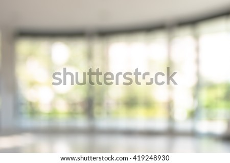 Blurred abstract background interior view looking out toward empty vacant office lobby and entrance doors and glass curtain wall frame: Blurry perspective of reception hall to building main entrance  - stock photo