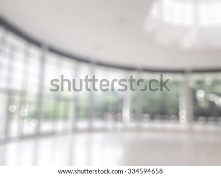 Blurred abstract background interior view looking out toward to empty office lobby and entrance doors and glass curtain wall with frame and sky light: Blur view of reception hall to building entrance - stock photo