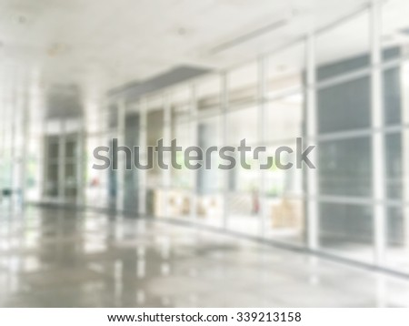 Blurred abstract background interior view looking out toward to empty office lobby and entrance doors - stock photo