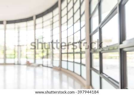 Blurred abstract background interior view looking out toward to empty office lobby and entrance doors and glass curtain wall with frame: Blurry perspective of reception hall to building entrance   - stock photo
