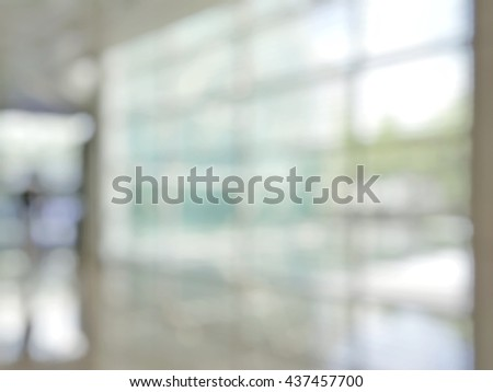 Blurred abstract background interior view looking out toward to empty office lobby and entrance doors and glass curtain wall with frame: Blurry perspective of reception hall to building entry/ exit - stock photo