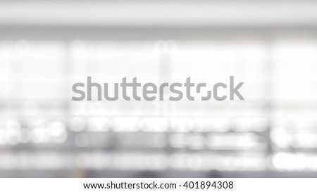 Blurred abstract background interior view looking out toward to empty office lobby, corridor walk way and glass curtain wall with frame and light: Blur view of reception hall to building window facade - stock photo