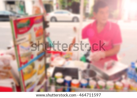 Blurred abstract background of A man selling ice cream on a cart.