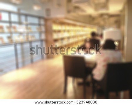 Blurred abstract background of a view of aisle of book shelves in public library: Blurry interior perspective of a study room with tables, chairs and stacks of books: Blur educational interior   - stock photo