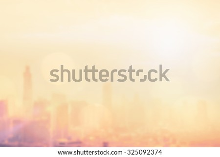 Blurred abstract background of bright vintage gold light of downtown Bangkok cityscape with sun flare and bokeh in warm color tone: Blurry holiday eco city travel backgrounds of urban morning sunrise  - stock photo