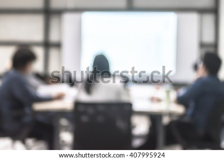 Blurred abstract background of business discussion people group or educational presentation in meeting room with projector slide screen in front of table, chair: Blurry view inside office interior - stock photo