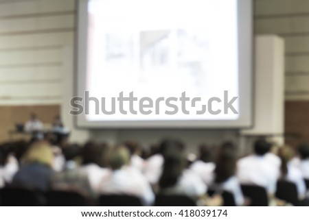 Blurred abstract background of business/ educational conference seminar with speakers in auditorium hall on stage with projector screen presentation with audiences/ students sitting in seat rows - stock photo