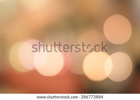 Blurred abstract background of candle light bokeh in warm yellow orange color tone