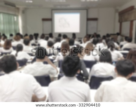 Blurred abstract background of college students sitting in seating rows attending school course: Blurry view from back of the classroom toward projector screen presentation in front of the class - stock photo