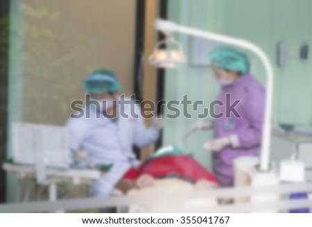 Blurred abstract background of dentistry care unit room interior in dental hospital/ clinic with dentist and assistants working on patient's tooth care using equipment, instrument on dental chair