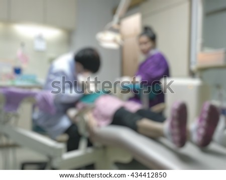 Blurred abstract background of dentistry care unit room interior in dental hospital/ clinic with dentist and assistants working on patient's tooth oral care using equipment, instrument on dental chair - stock photo
