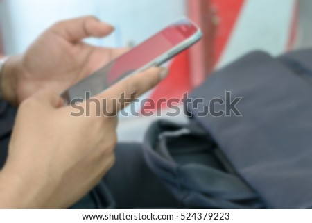 Blurred abstract background of hand women use smartphone and bag
